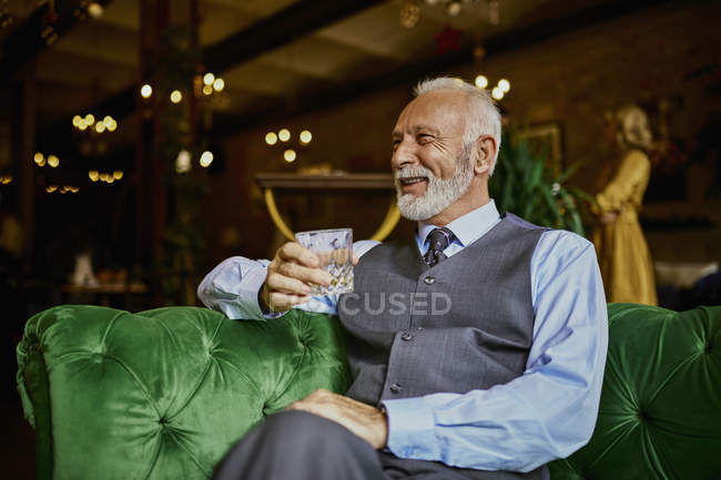 Portrait of elegant senior man sitting on couch in a bar and holding tumbler — Stock Photo