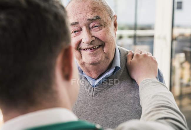 Homme aîné souriant au jeune homme — Photo de stock