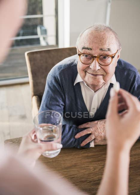 Pillet de fixation de femme et verre d'eau pour l'homme aîné de sourire — Photo de stock