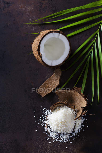 Открытый кокосовый орех, кокосовая шелуха и куча кокосовых хлопьев — стоковое фото