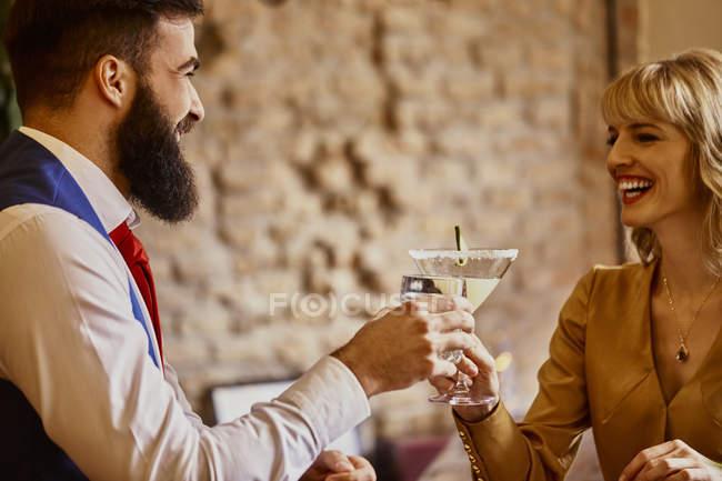 Glückliches elegantes Paar beim Anstoßen auf Gläser in einer Bar — Stockfoto