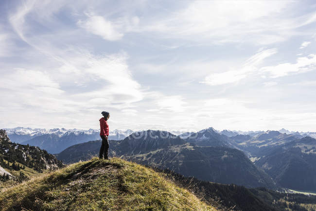 Austria, Tyrol, young woman standing in mountainscape and looking at view — Stock Photo