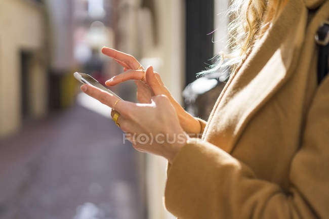 Closee-up of young woman on a lane using cell phone — Stock Photo