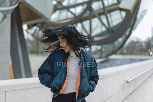 Francia, Parigi, sorridente giovane donna gettando i capelli — Foto stock