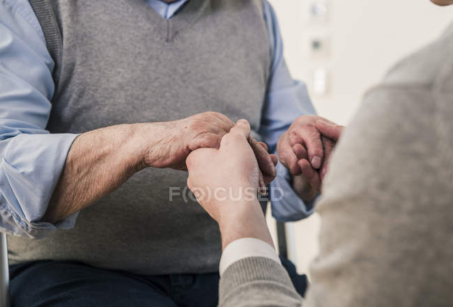 Close-up of senior man and young man holding hands — Stock Photo