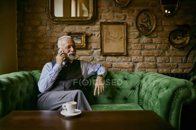 Elegant senior man sitting on couch in a cafe and talking on cell phone — Stock Photo