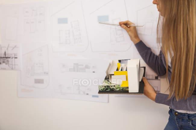 Architektin arbeitet an einem Projekt und hält Architekturmodell in der Hand — Stockfoto
