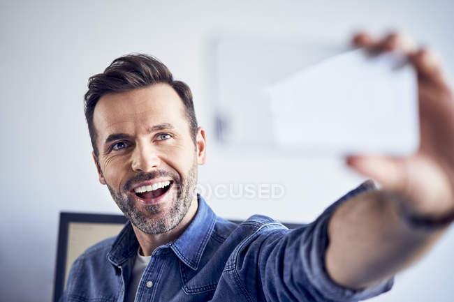 Felice uomo in ufficio prendendo selfie — Foto stock