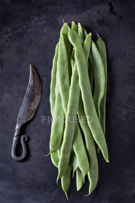 Französische Bohnen und ein altes Messer auf dunklem Metall — Stockfoto