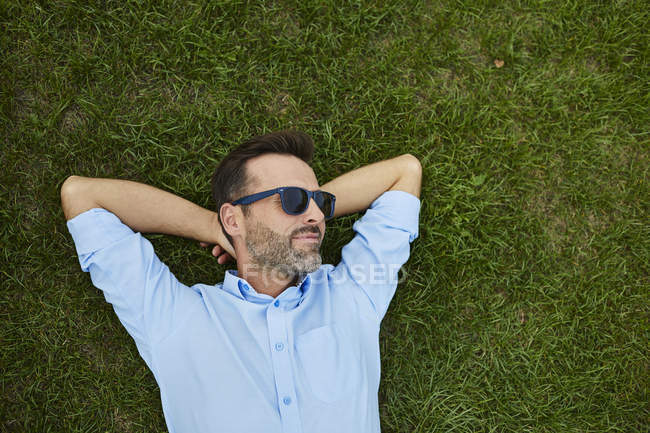 Man wearing sunglasses relaxing on meadow, top view — Stock Photo
