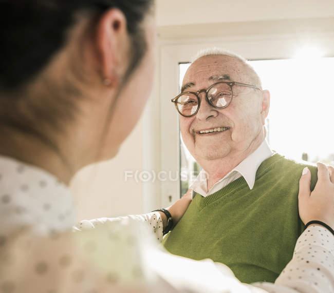 Homme aîné souriant à la jeune femme — Photo de stock