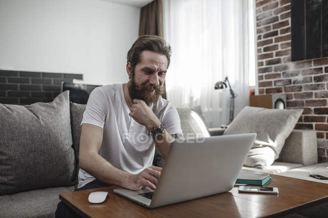 Smiling man sitting on the couch at home and using laptop — Stock Photo
