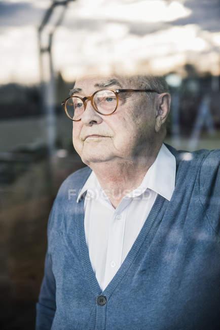 Verticale d'homme aîné sérieux à la fenêtre — Photo de stock