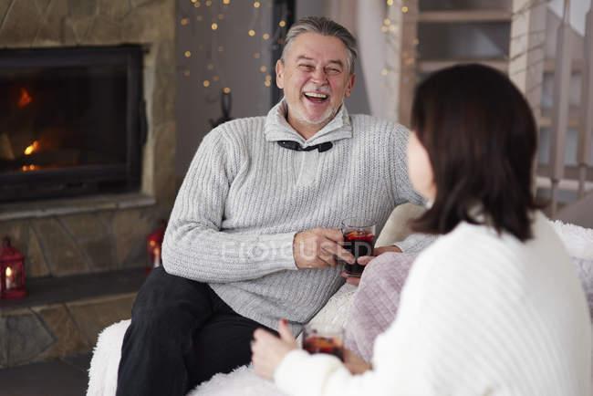 Feliz casal maduro com bebidas quentes na sala de estar — Fotografia de Stock