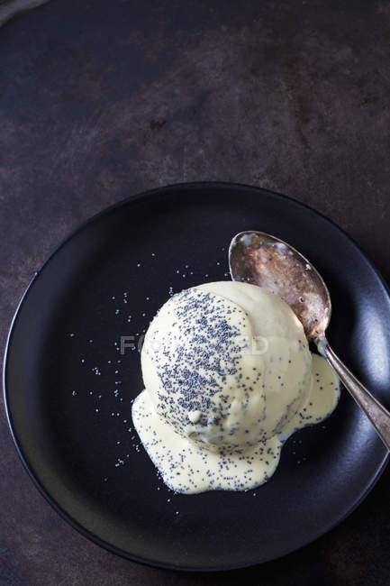 Дрожжевые пельмени с ванильным соусом и семенами мака на тарелке — стоковое фото