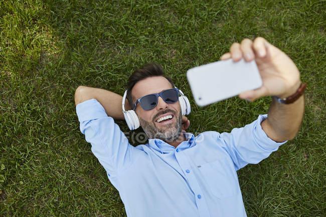Portrait d'homme riant allongé sur la prairie prenant selfie avec smartphone, vue de dessus — Photo de stock