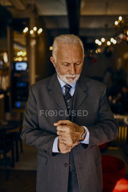 Elegante uomo anziano che si aggiusta le manette — Foto stock