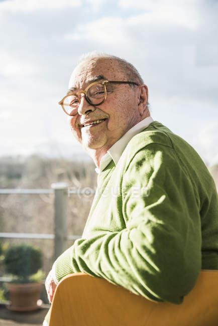 Verticale d'homme aîné de sourire s'asseyant sur la présidence à la fenêtre — Photo de stock