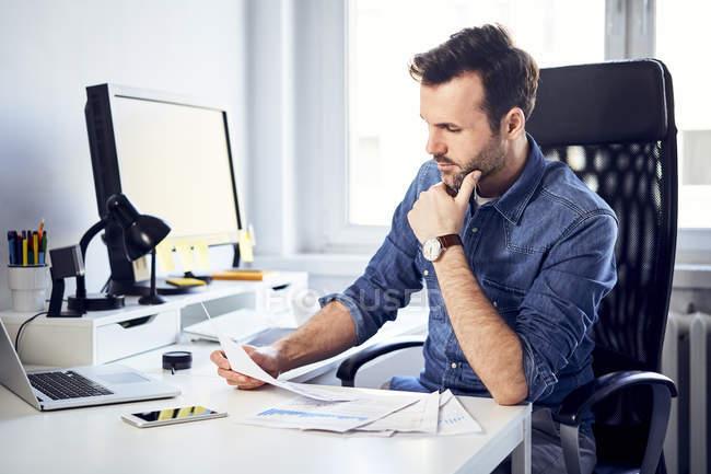 Людина читає документ на столі в офісі — стокове фото