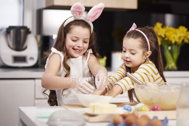 Duas irmãs se divertindo cozinhando biscoitos de Páscoa na cozinha juntas — Fotografia de Stock