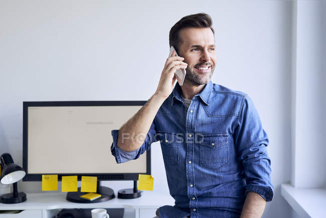 Улыбающийся человек за столом в офисе разговаривает по телефону — стоковое фото