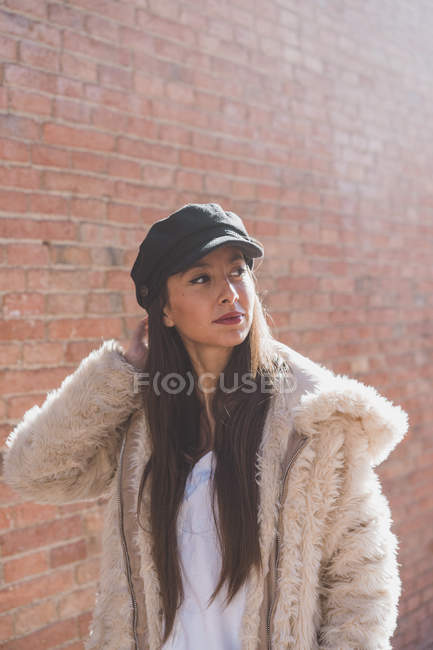Stylish young woman in front of brick wall — Stock Photo