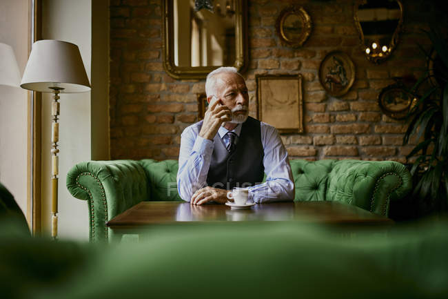 Elegant senior man sitting on couch in a cafe on cell phone — Stock Photo