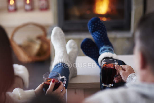Mature couple with hot drinks in living room at the fireplace — Stock Photo