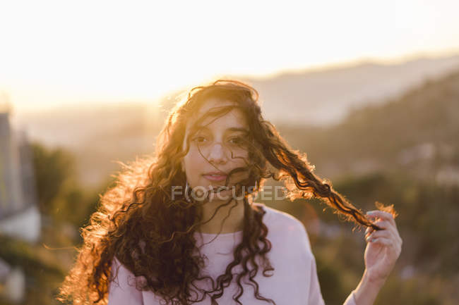 Portrait of young woman with long curly hair at sunset — Stock Photo