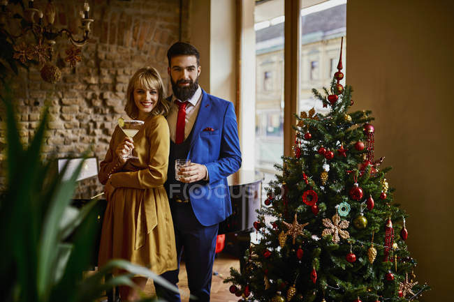 Portrait of elegant couple with drinks at Christmas tree — Stock Photo