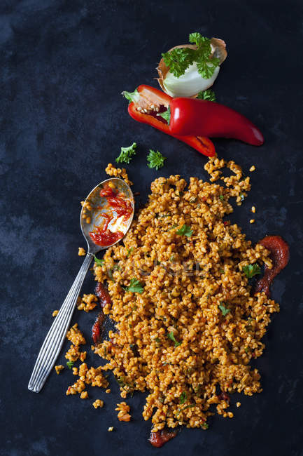 Bulgur wheat salad and ingredients on dark ground — Stock Photo