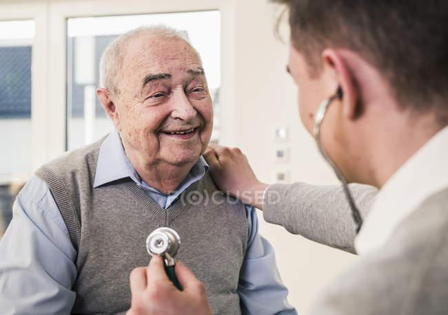 Senior lächelt Krankenschwester zu Hause mit Stethoskop an — Stockfoto