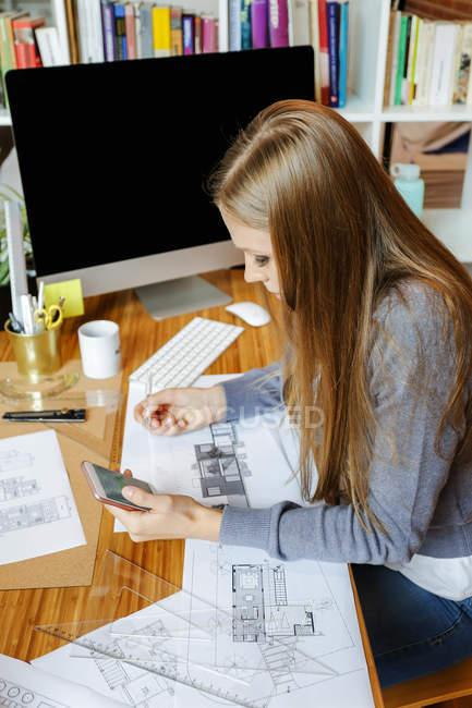 Mujer joven que trabaja en la oficina de arquitectura, usando el teléfono - foto de stock