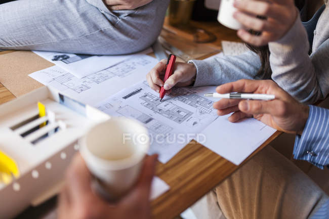 Team of architects working on a project, discussing blueprints — Stock Photo