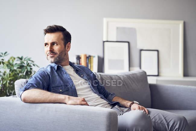 Souriant homme détendu assis sur le canapé et regardant loin — Photo de stock