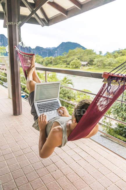 Лаос, Ванг Виенг, молодой человек, лежащий в гамаке с ноутбуком — стоковое фото