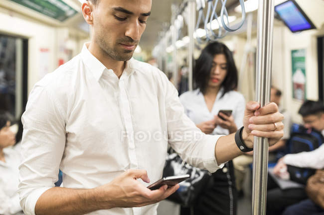 Businessman and businesswoman using cell phones in the subway — Stock Photo