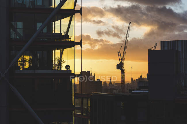 UK, London, buildings and crane silhouette at sunset with Big Ben and Westminster in far background — Stock Photo