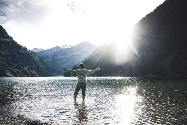 Austria, Tyrol, hiker standing with outstretched arms in mountain lake — Stock Photo