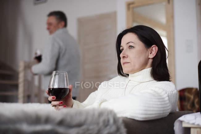 Ernste reife Frau mit einem Glas Wein und Mann im Hintergrund — Stockfoto