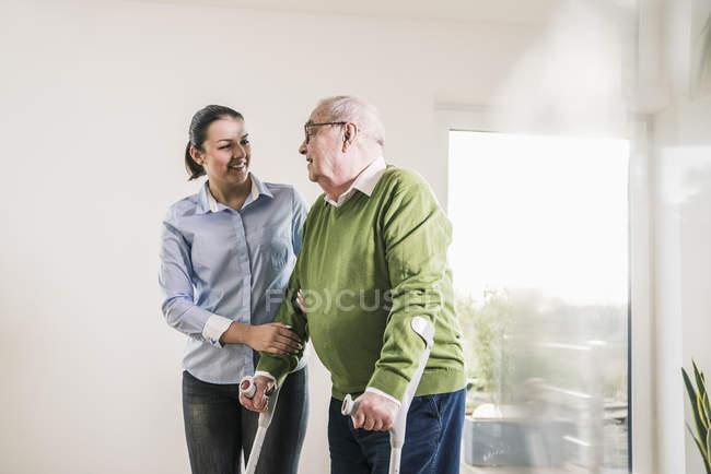 Jeune femme soutenant l'homme aîné marchant sur des béquilles — Photo de stock