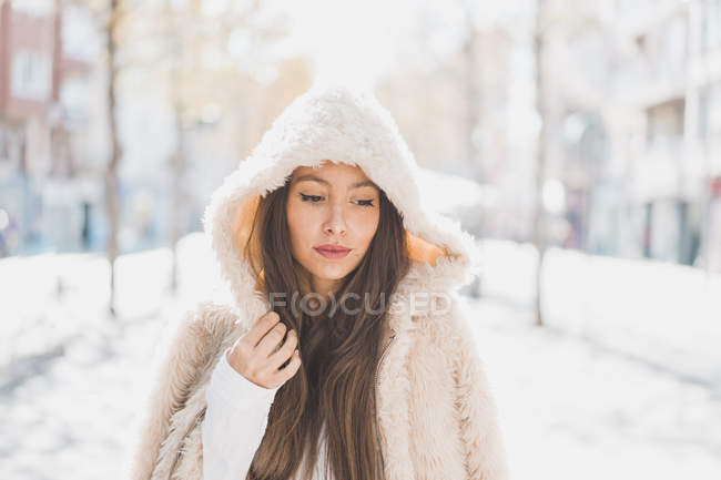 Portrait of young woman wearing hooded fur jacket — Stock Photo