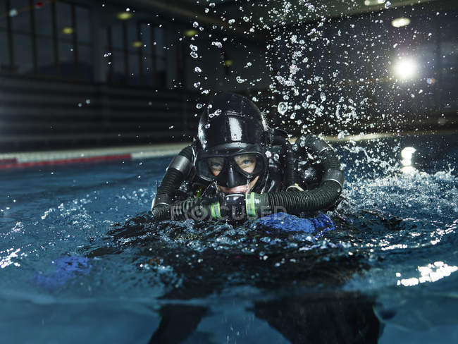 Female scuba diver training in swimming pool — Stock Photo