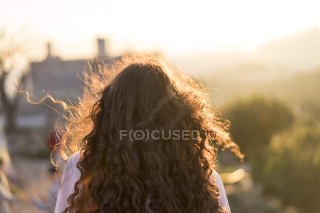 Обратный вид молодой женщины с длинными вьющимися волосами на закате — стоковое фото