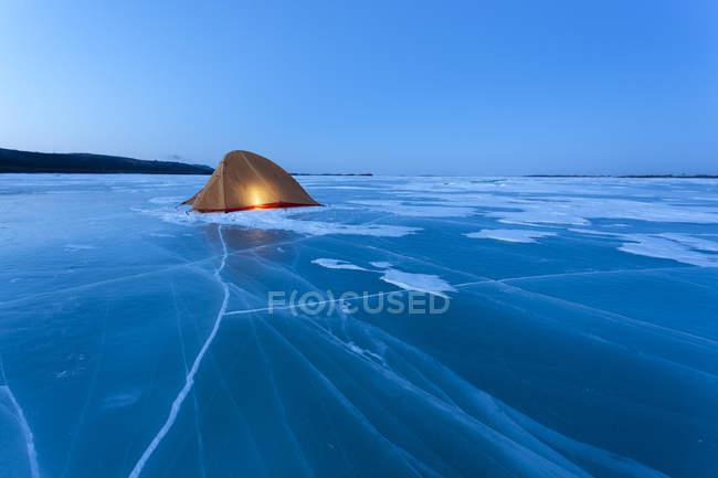 Russland, amur oblast, beleuchtetes zelt auf gefrorenem zeya fluss zur blauen stunde — Stockfoto
