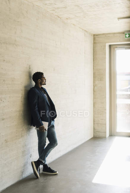 Businessman standing at concrete wall and looking away — Stock Photo