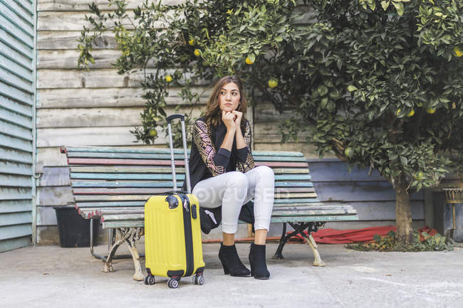 Young woman with travel bag waiting on bench — Stock Photo