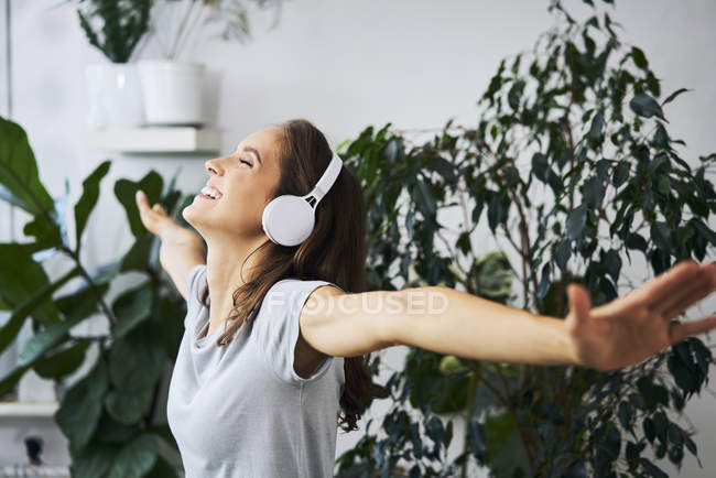 Happy young woman with outstretched arms listening to music near indoor plant — Stockfoto