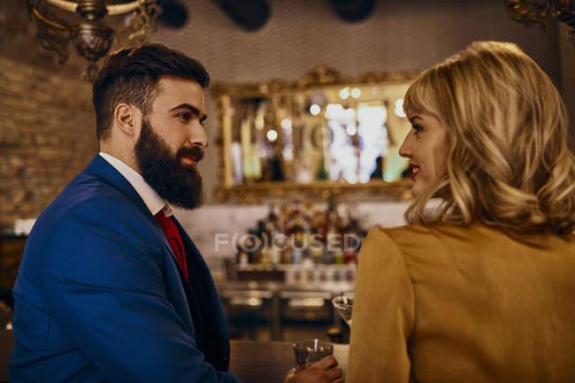 Elegantes Paar lächelt sich in einer Bar an — Stockfoto