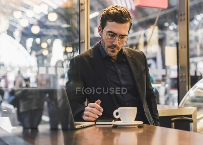 Jungunternehmer in einem Café am Bahnhof mit Tasse Kaffee, Laptop und Handy — Stockfoto